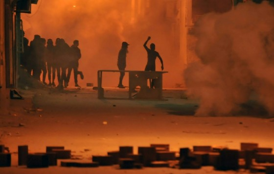 Protestors throw stones towards security forces in Tunis' Djebel Lahmer district early on January 10, 2018 after price hikes ignited demonstrations