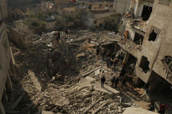Un cratere provocato da una bomba a Ghouta, Siria, dove sono morti almeno 30 bambini