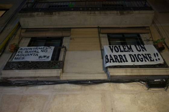 """A banner reading """"We want a dignified neighbourhood"""" hung from a balcony to protest drug flats in Raval, Barcelona"""