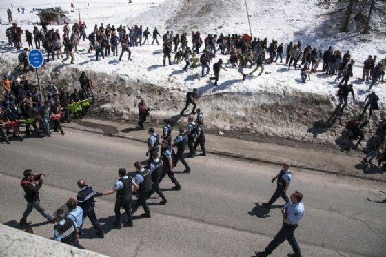 I manifestanti 'antifascisti' italo-francesi dei movimenti No Tav e Briser les frontieres aggirano il cordone della polizia francese durante il corteo al confine tra Italia e Francia di Monginevro