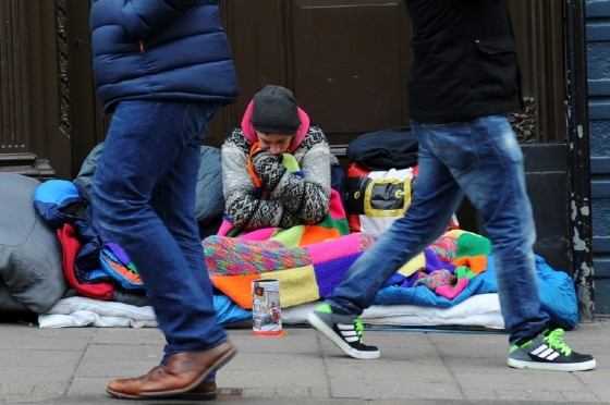 Pedestrians walk past homeless man Magic in his spot in a doorway on High Street opposite Windsor Castle