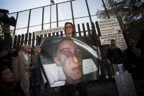 Ilaria Cucchi all'esterno della Procura di Roma con il manifesto che ritrae suo fratello morto