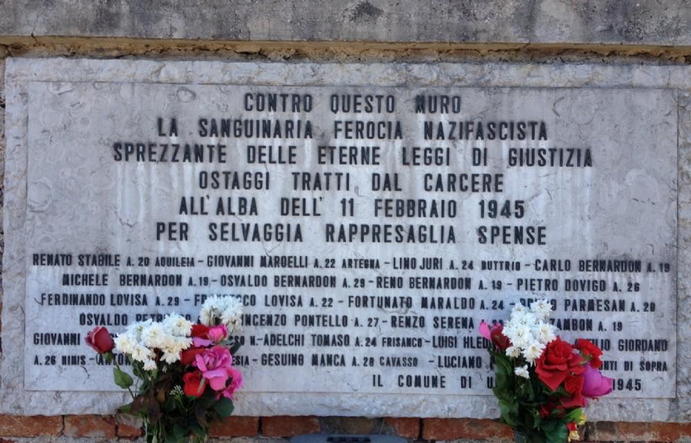La lapide a ricordo dei 23 partigiani fucilati davanti al cimitero