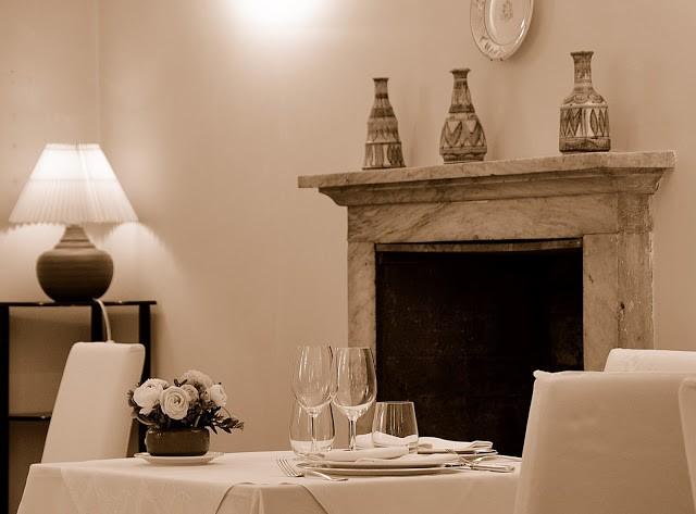 Un tavolo apparecchiato elegantemente davanti al caminetto