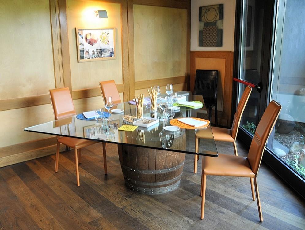 Il tavolo conviviale in cristallo nella sala con vista giardino