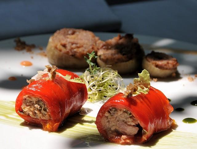 I peperoni arrostiti, spellati e ripieni di ventresca di tonno, accompagnano le dolci cipolli eporediesi farcite di amaretti e uvetta