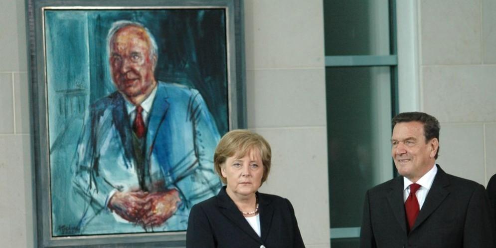 Angela Merkel con il suo predecessore Gerard Shroeder, davanti a un ritratto di Helmut Kohl.