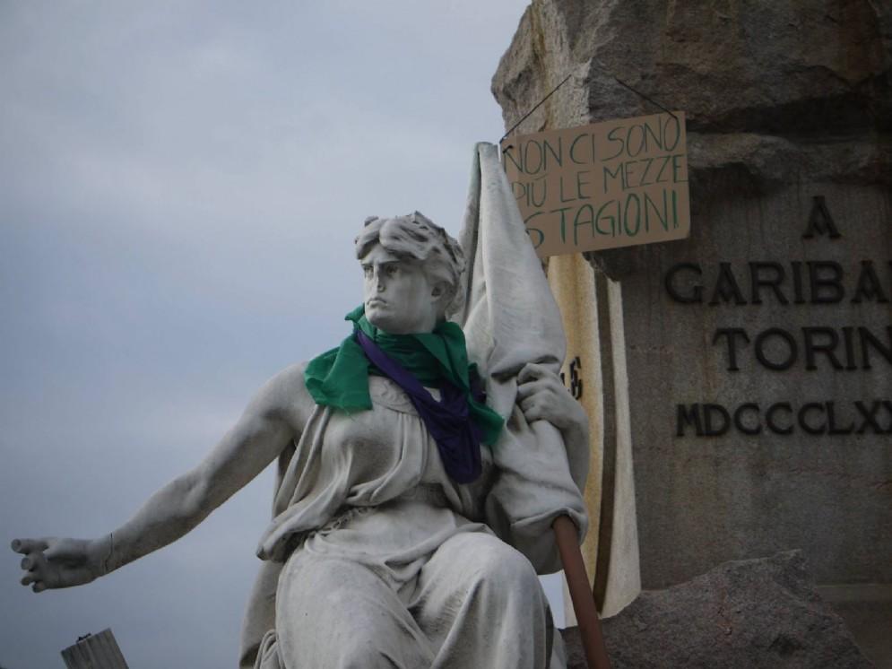 A Torino statue con sciarpe e cappelli