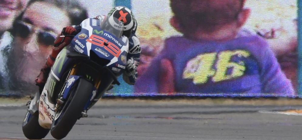 Jorge Lorenzo passa davanti a un cartello dei tifosi di Valentino Rossi ad Aragon