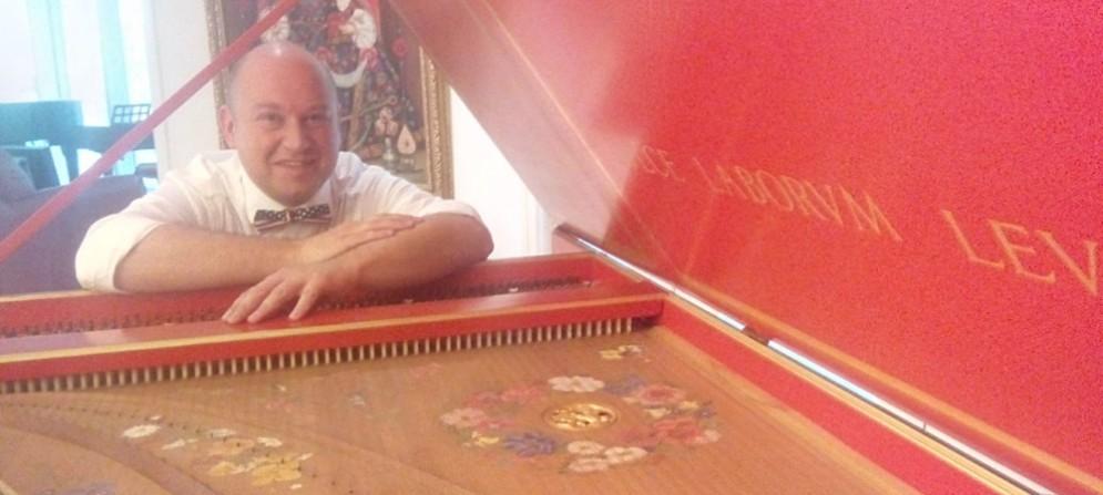 Alberto Busettini sorridente accanto al suo clavicembalo