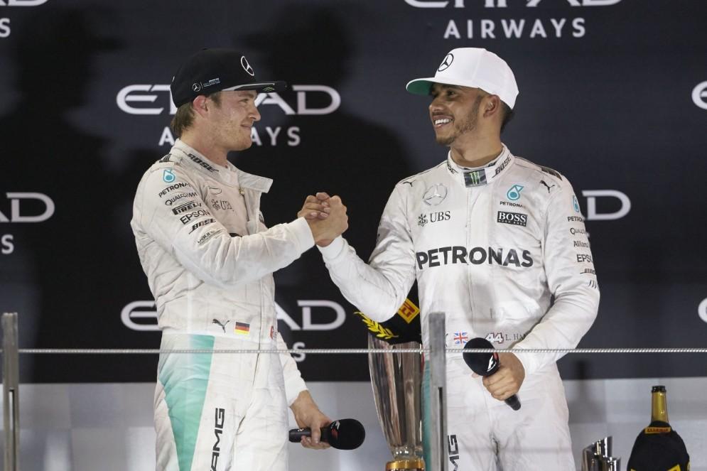 Nico Rosberg e Lewis Hamilton si stringono la mano sul podio di Abu Dhabi
