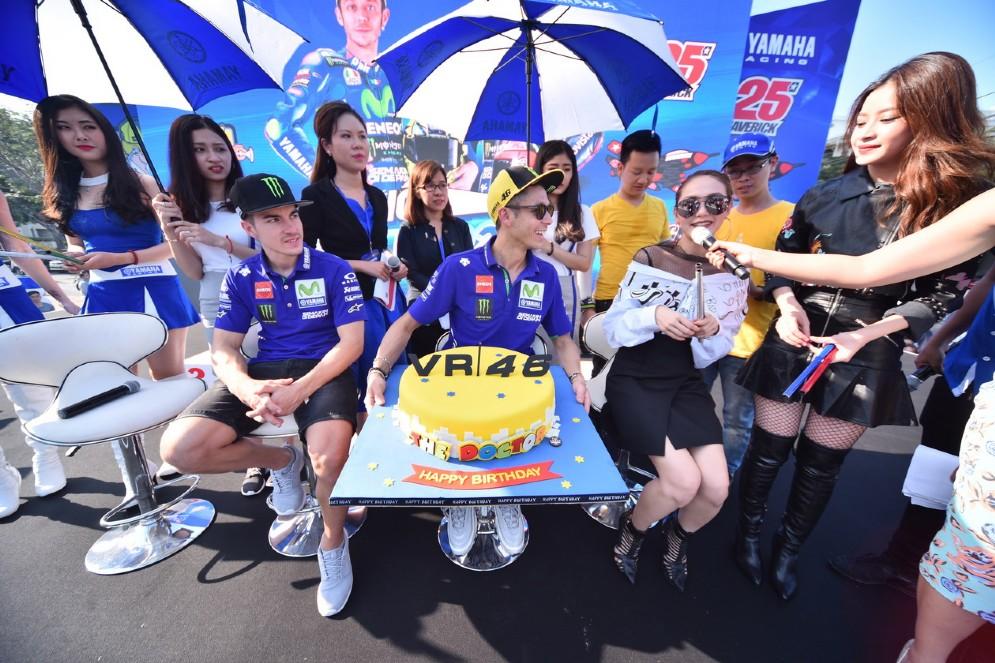 Valentino Rossi con la sua torta di compleanno sul palco insieme a Maverick Vinales