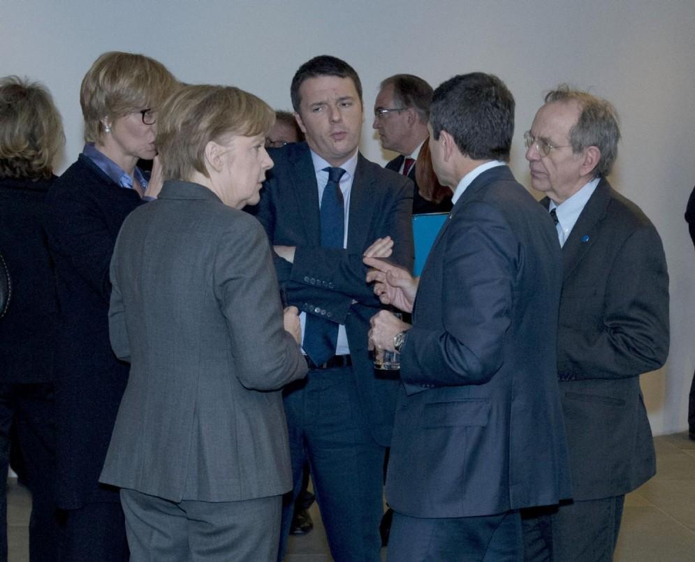 La cancelliera tedesca Angela Merkel con il ministro Padoan e l'ex premier Renzi