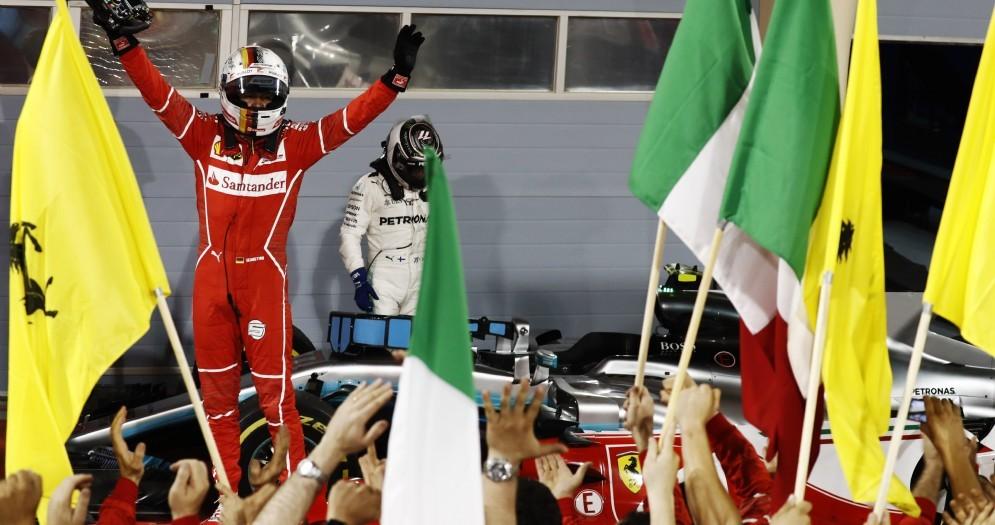 Le braccia alzate di Sebastian Vettel davanti a un deluso Valtteri Bottas