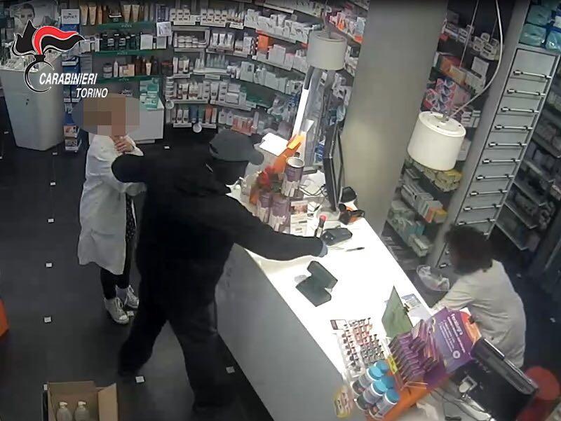 Il rapinatore in azione dentro la farmacia