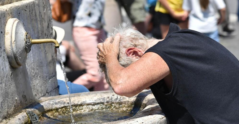 Un anziano si bagna la testa in una giornata particolarmente afosa