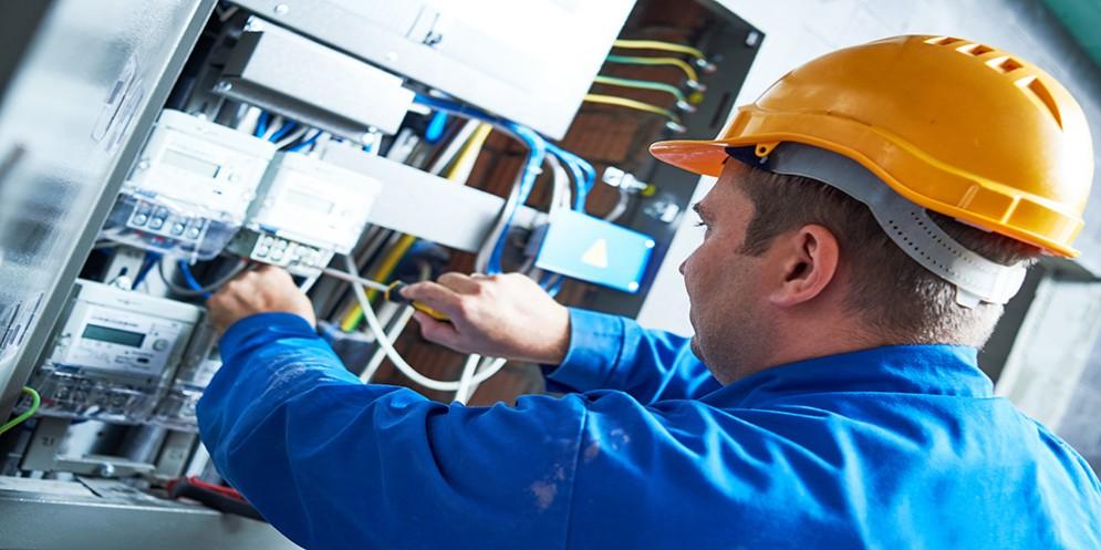 Un tecnico di fronte a un contatore dell'energia elettrica