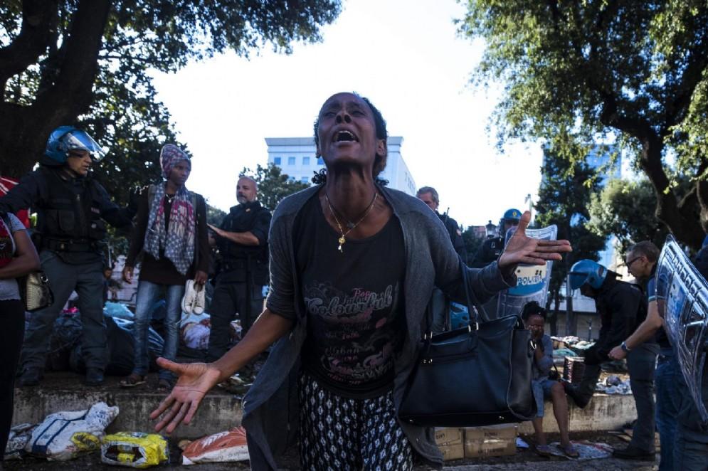 Una donna piange in mezzo alle forze dell'ordine e ai profughi sgomberati