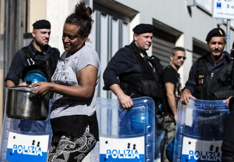 Una donna con una pentola, sullo sfondo le forze dell'ordine