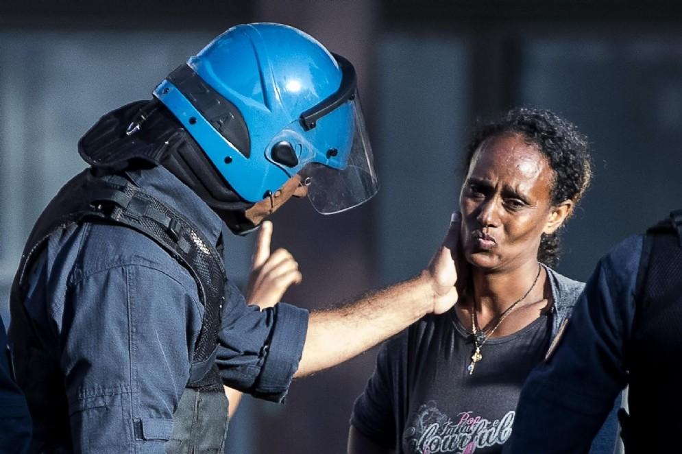 Un poliziotto accarezza il volto della donna nel tentativo di consolarla