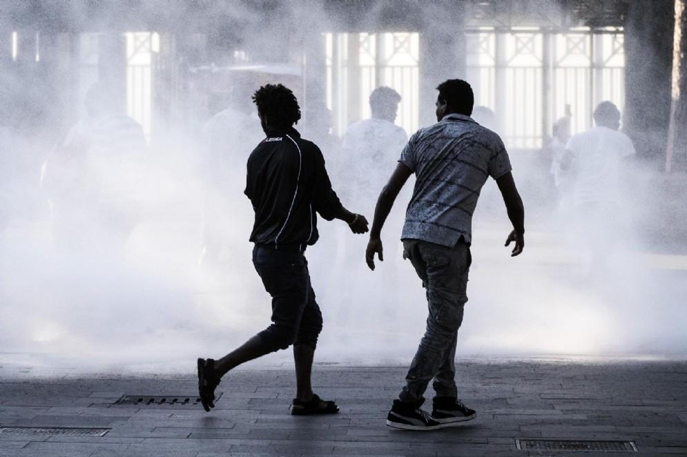 Profughi cercano riparo dal getto degli idranti della polizia