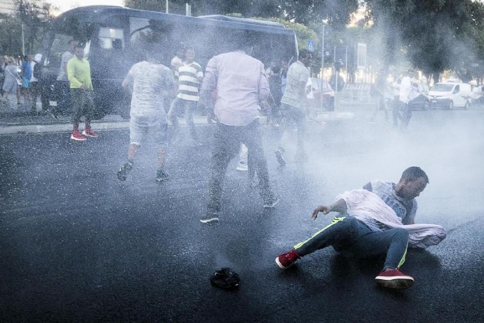 Un rifugiato atterrato dal getto degli idranti della polizia