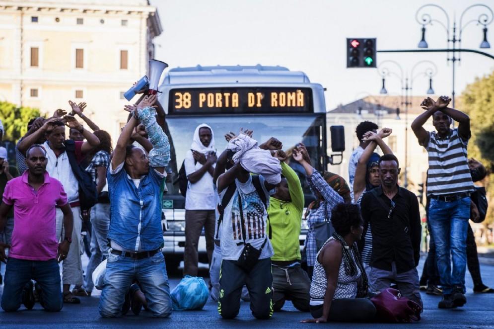 I profughi sgomberati fanno il gesto delle manette in segno di protesta