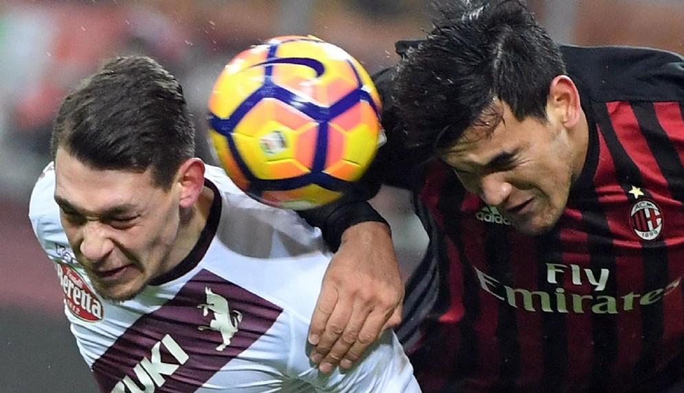 Il difensore del Milan Gomez a contrasto con Belotti