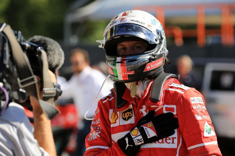 Vettel saluta le telecamere dopo essere sceso dalla sua macchina