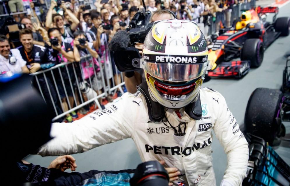 Hamilton festeggia con il team Mercedes dopo aver vinto la gara