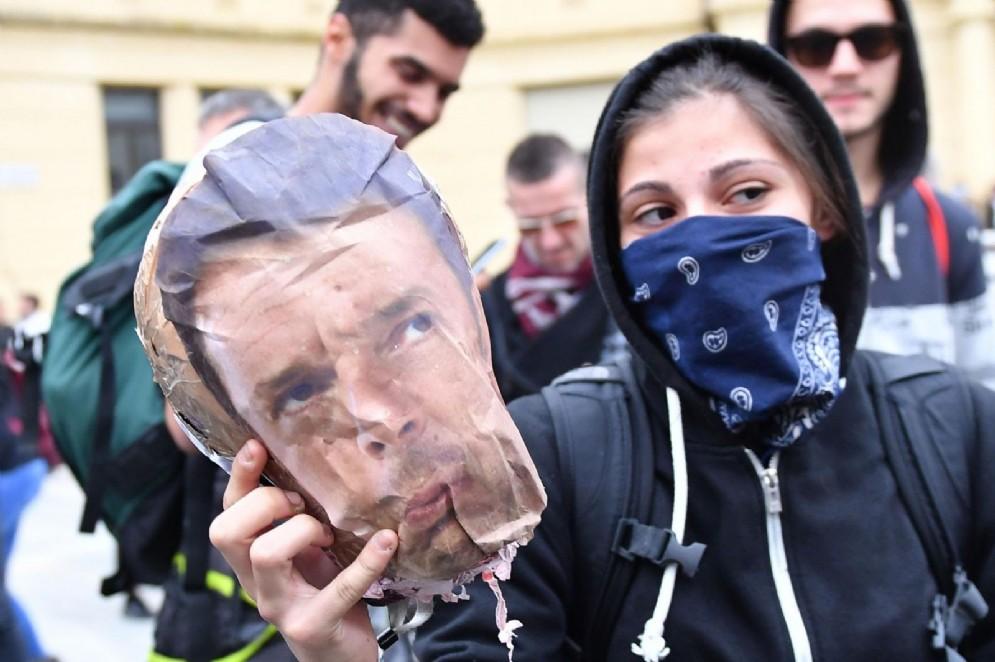 Una ragazza mostra la maschera di Matteo Renzi