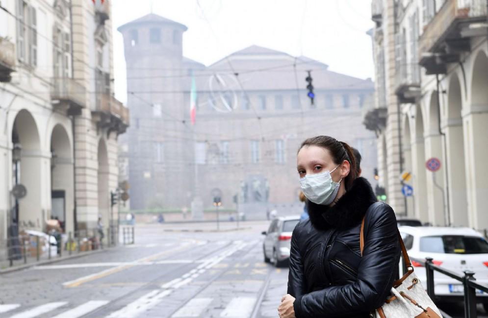 Una ragazza si protegge con una mascherina dallo smog di Torino