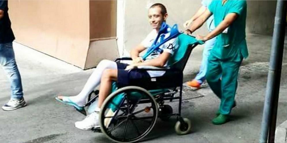Valentino Rossi in uscita dall'ospedale di Ancona in sedia a rotelle e con il gesso alla gamba