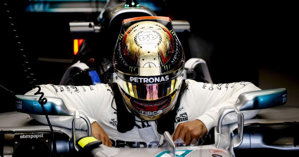 Lewis Hamilton si cala nell'abitacolo della sua Mercedes