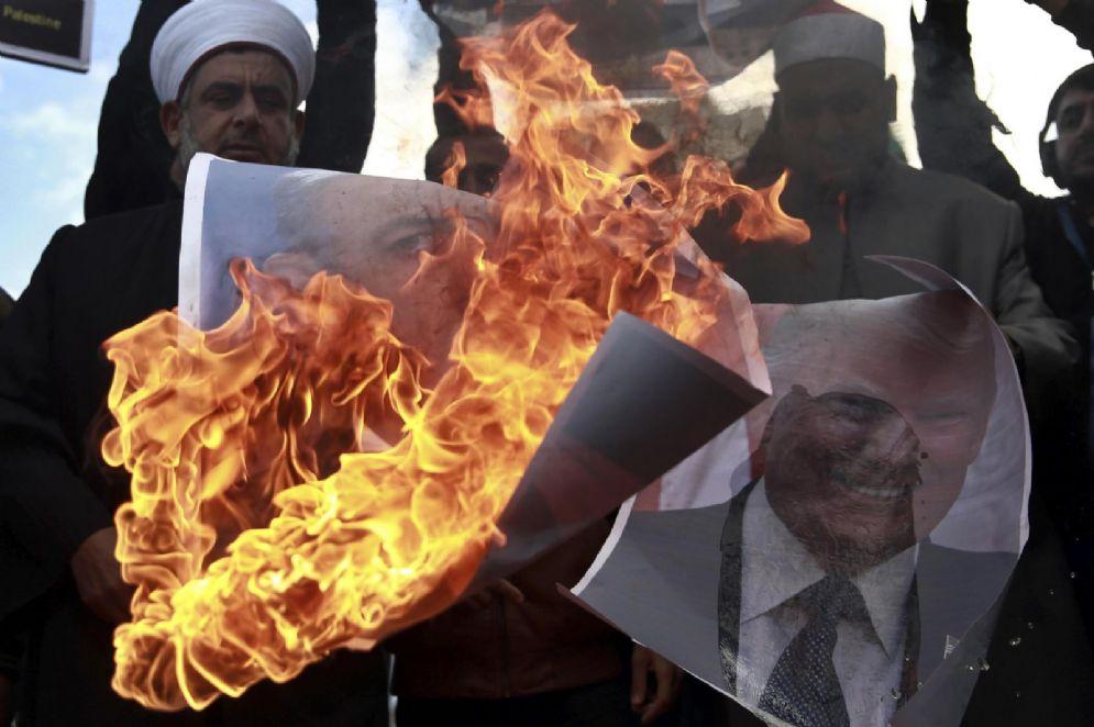Palestinesi bruciano manifesti con i volti del primo ministro israeliano Benjamin Netanyahu e quello Usa Donald Trump