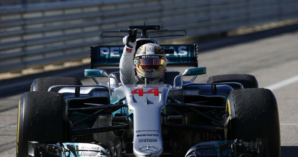 Lewis Hamilton esulta a braccia alzate al volante della Mercedes