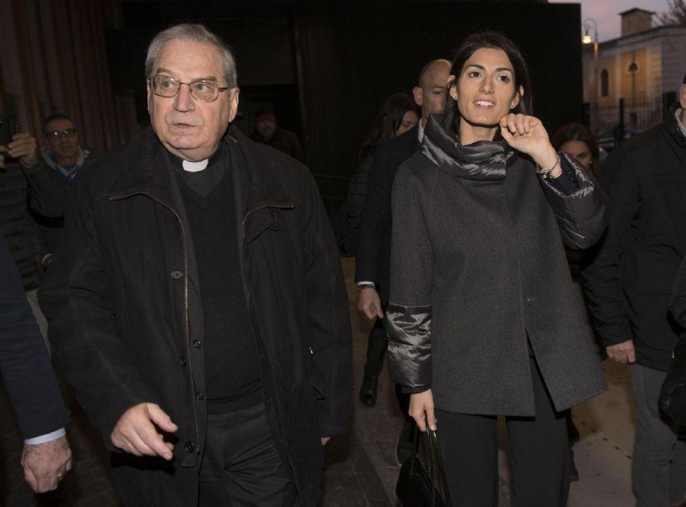 La sindaca di Roma Virginia Raggi (d) e il direttore della Caritas Mons. Enrico Feroci, durante la messa di Natale presso l'Ostello ''Don Luigi Di Liegro'' alla stazione Termini a Roma, 24 dicembre 2016. ANSA/GIORGIO ONORATI