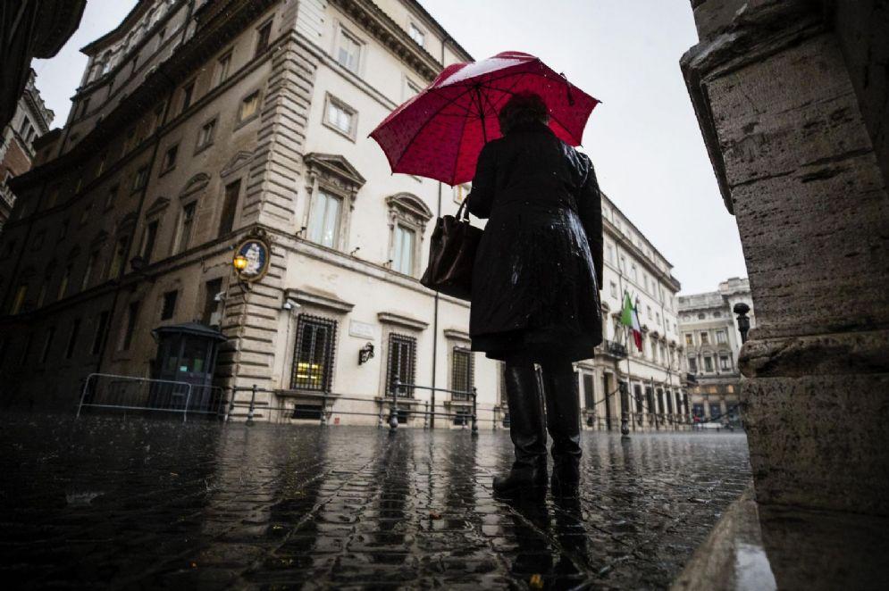 Una persona si ripara con l'ombrello sotto la pioggia in piazza Colonna a Roma