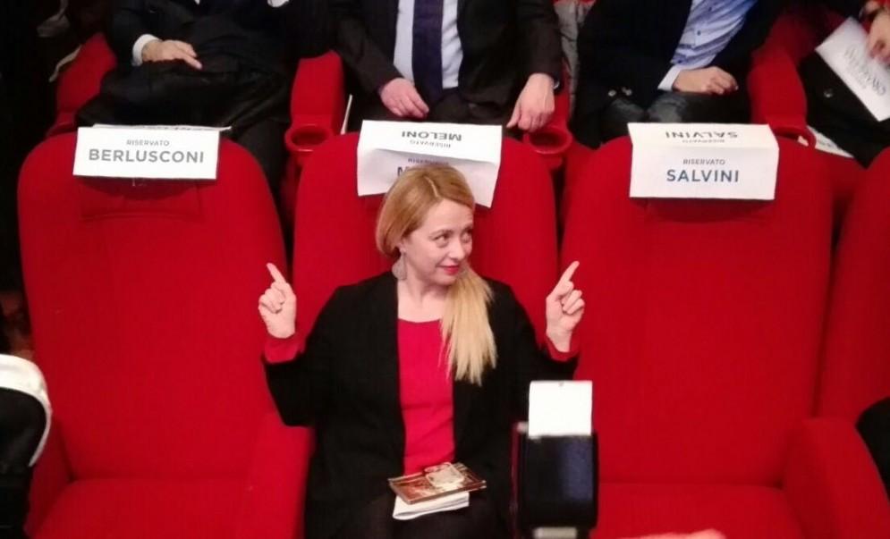 Giorgia Meloni in mezzo alle sedie lasciate vuote da Silvio Berlusconi e Matteo Salvini