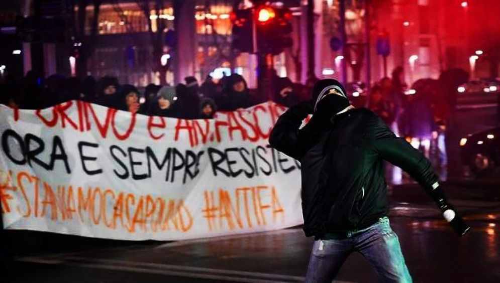 Un manifestante lancia un oggetto contro la polizia