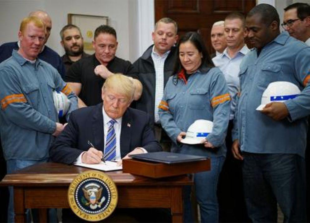 Il presidente Usa Donald Trump circondato da un gruppo di operai mentre firma l'approvazione dei dazi sull'acciaio