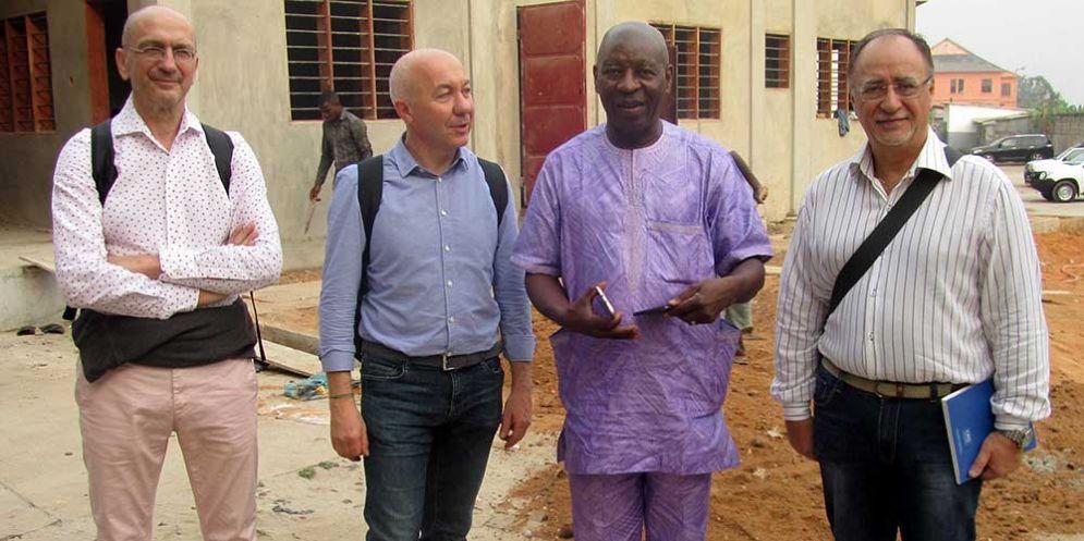 Da sinistra a destra: Sopracordevole,Borsatti, Amoussou-Guenou e Canzonieri davanti a un padiglione in costruzione dell'Ospedale St. Luc di Cotonou