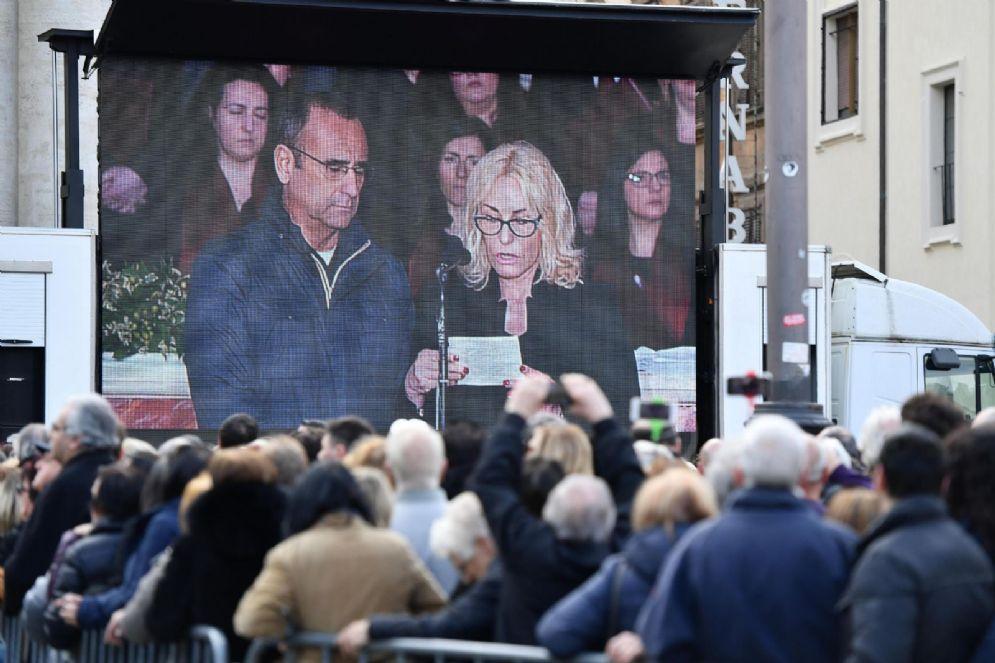 Carlo Conti e Antonella Clerici sul maxischermo all'esterno della chiesa degli Artisti durante i funerali di Fabrizio Frizzi, Roma, 28 marzo 2018.