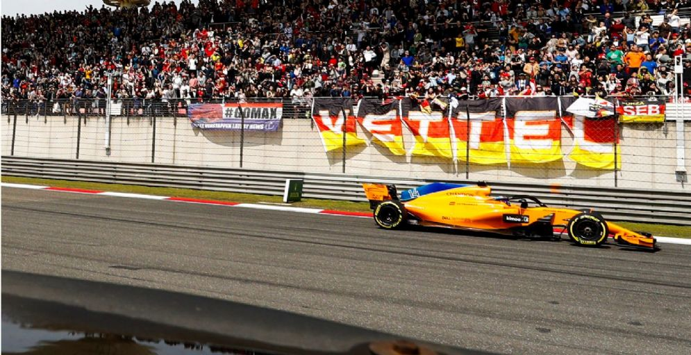La McLaren di Fernando Alonso passa sotto allo striscione dei tifosi di Sebastian Vettel durante il GP di Cina di F1