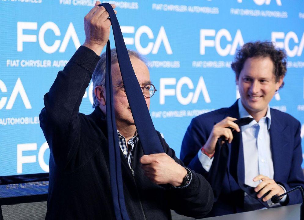 """Sergio Marchionne e John Elkann al termine dell'evento """"FCA Capital Markets Day"""" dal maxi schermo della sala stampa a Balocco, Torino"""