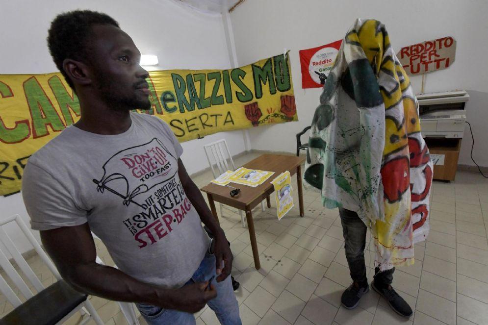 """Un momento della conferenza stampa all'interno degli spazi dell'EX Capanificio di Caserta alla quale ha preso parte il migrante, nascosto da un telo, che è stato ferito da sconosciuti che gli hanno urlato contro '' Salvini, Salvini"""""""