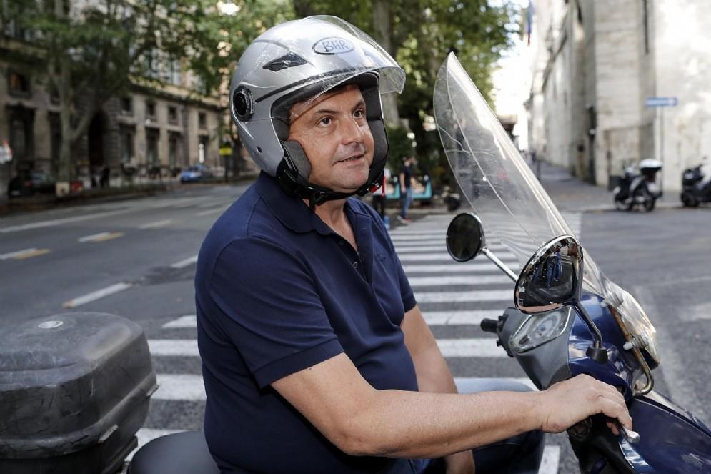 Carlo Calenda, ex ministro dello Sviluppo Economico, di passaggio con lo scooter