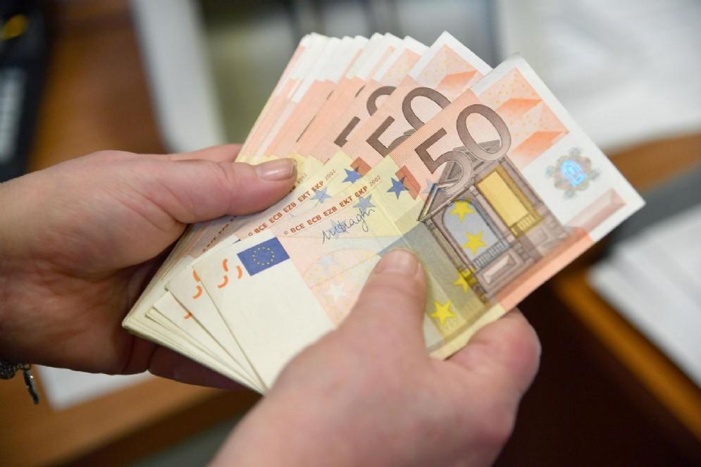 Alcune banconote da 50 Euro in mano a un cassiere di una banca