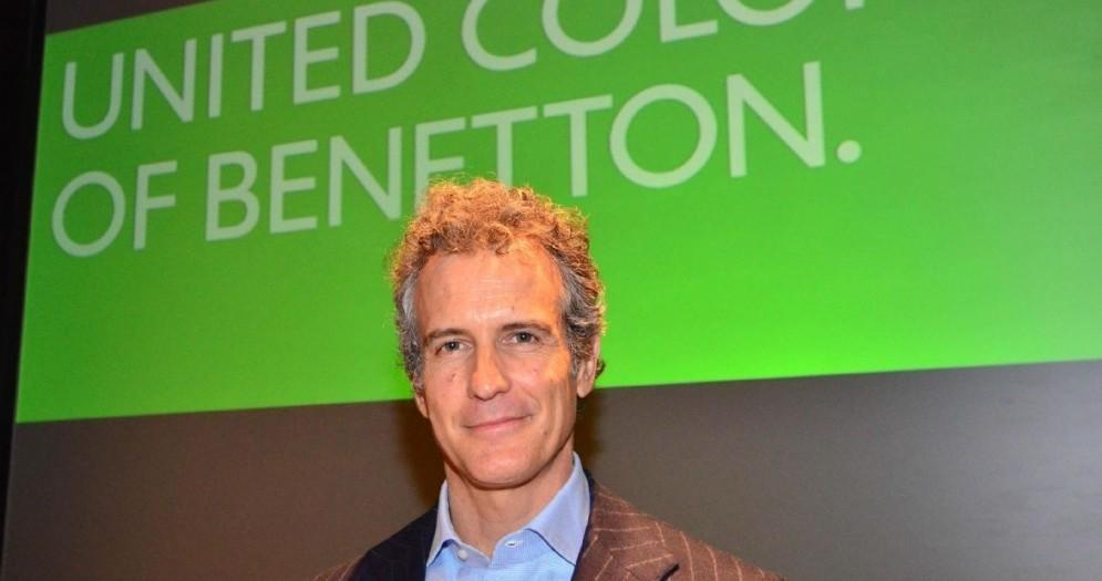 Alessandro Benetton posa sorridente accanto al logo dell'azienda