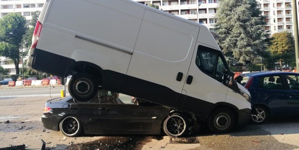 Perde il controllo della BMW che finisce sotto un furgone